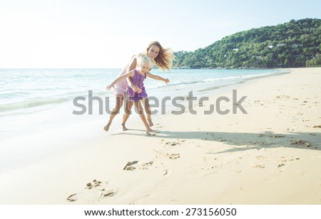 games on the beach. mom and daughter playing together - stock photo