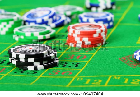 Gaming chips on the green cloth casino. High detailed photo - stock photo