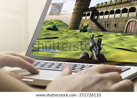 gaming concept: man using a laptop to play war game - stock photo