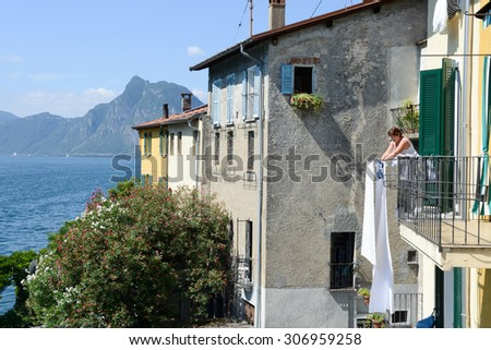 Gandria, Switzerland - 3 August 2015: Woman stretching out the linen on her  terrace in Gandria on Lake Lugano in Switzerland