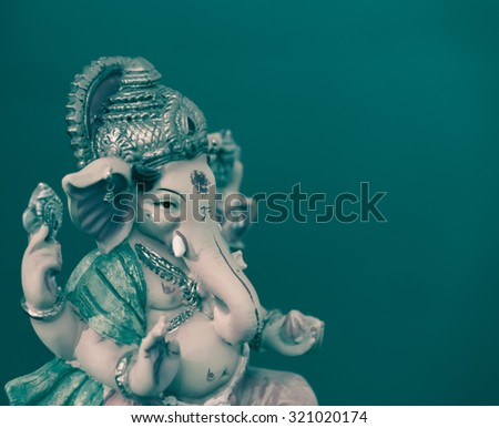 Ganesh (Ganapati- Elephant God) in Hindusim mythology closeup hold the weapons maze and axe pose right side green split-tone - stock photo