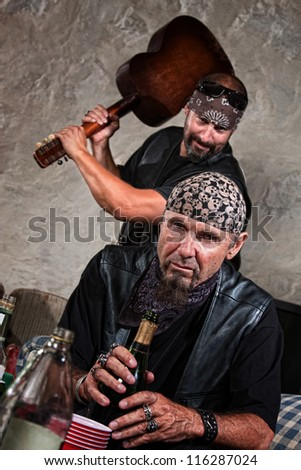 Gang member with guitar about to attack man sitting