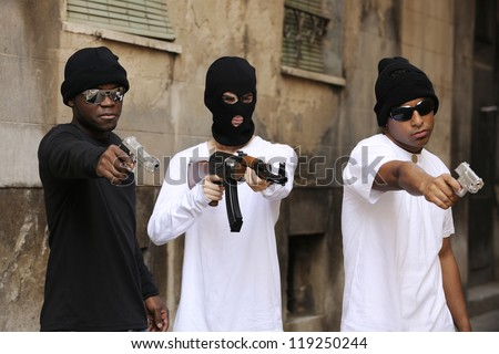 Gang members or guerrilla with gun and rifle on the street - stock photo