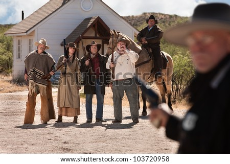 Gang of outlaws with rifles in old American west town - stock photo