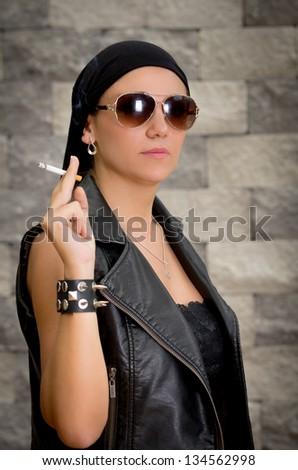 gang woman smokes on the street, selective focus - stock photo