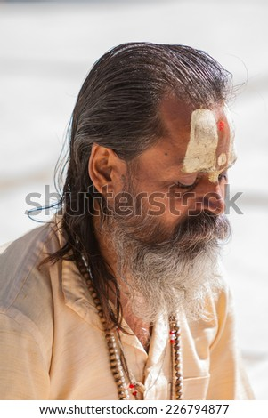 GANGOTRI, INDIA - MAY 23rd - A Hindu priest sits in the temple courtyard to read Vedic scriptures in Gangotri on 23rd May 2013.