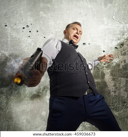 Gangster fires back with a gun in his hand on a wall background