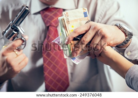 Gangster hijacks money, studio shoot - stock photo