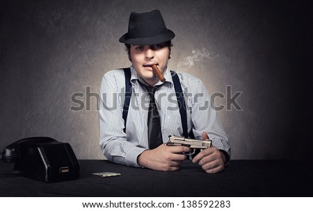 gangster holding a gun and smoking a cigar looking at camera on grunge background