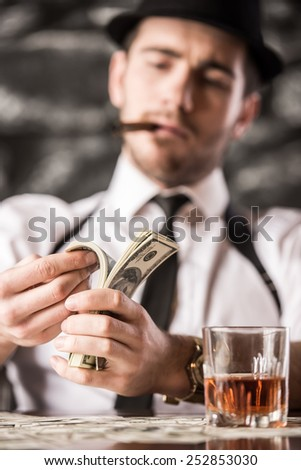 Gangster in shirt and suspenders is counting money and smoking Cuban cigar, while sitting at the table.