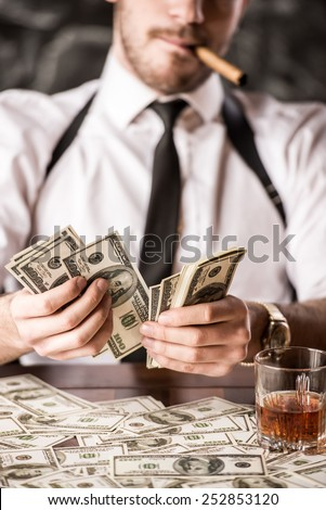 Gangster in shirt and suspenders is counting money and smoking Cuban cigar, while sitting at the table. - stock photo