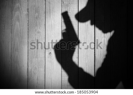 Gangster or investigator or spy silhouette on natural wooden wall. You can see more silhouettes and shadows on my page. - stock photo