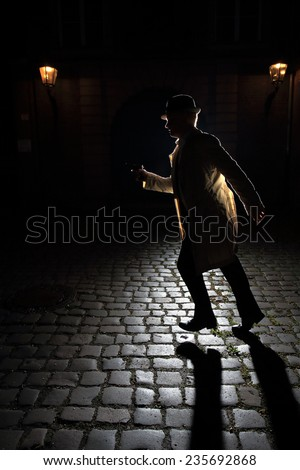 "Gangster wearing a classic trench coat. The man is running on cobblestone with a gun in his hand. The light creates a long shadow towards the viewer. Image inspired by ""film noir"" movies of the 1940s. - stock photo"