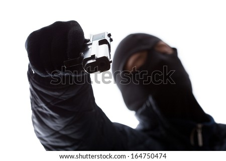 Gangster wearing a mask holding a gun - stock photo