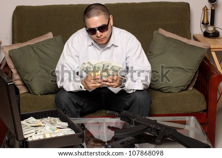 Gangster with bundles of cash, and guns. - stock photo