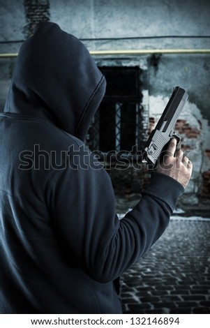 Gangster with gun in ghetto at night - stock photo