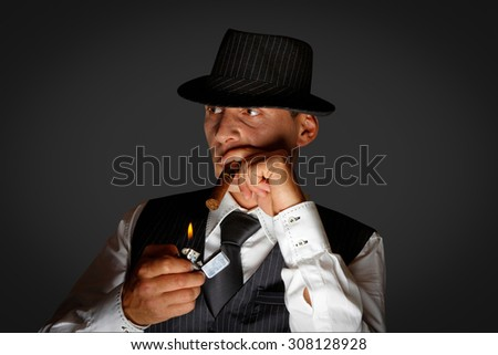gangster with hat smoking cigar, studio shot
