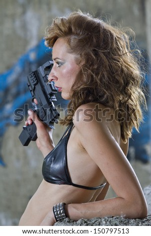 Gangster Woman with handgun in profile, posing outdoor