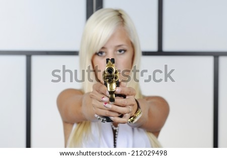 Gangster woman with pistol isolate to the background. Sensual female blonde bandit points snub nose revolver handgun weapon with focus on gun. - stock photo