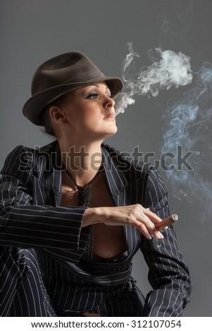 Gangster women smoking cigar, isolated on gray background