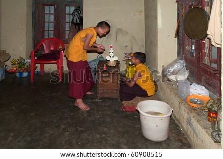 GANGTOK, SIKKIM, INDIA - MAY 17: Two unidentified little monks makes butter-sculptures to prepare a puja on May 17, 2010 in Enchey Gompa, Gangtok, Sikkim, India - stock photo