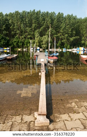 Gangway of planks over flooded river. - stock photo