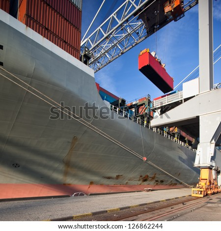 Gantry crane unloading container ship - stock photo