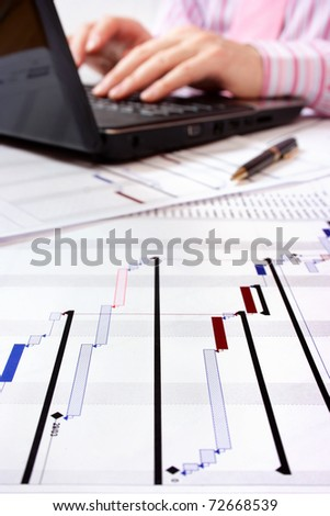 Gantt chart with project manager working on laptop in background. Selective focus on foreground. - stock photo