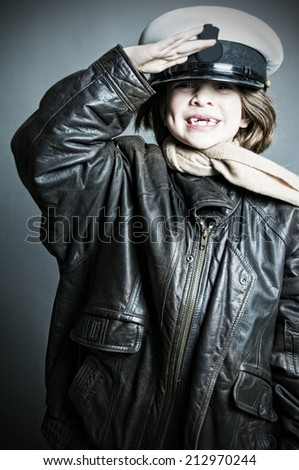 Gap-toothed girl in military cap saluting - stock photo