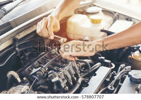 garage auto car service professional mechanic man checking and fixing car engine machine automobile mechanic