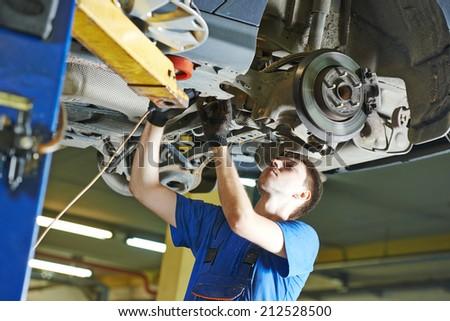 garage auto mechanic repairman checking car suspension during automobile maintenance at repair service station - stock photo