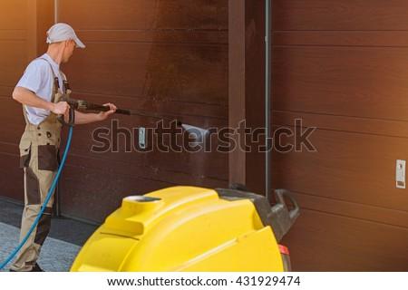Garage Door Washing by High Pressured Water. Caucasian Men Cleaning Garage Doors. - stock photo