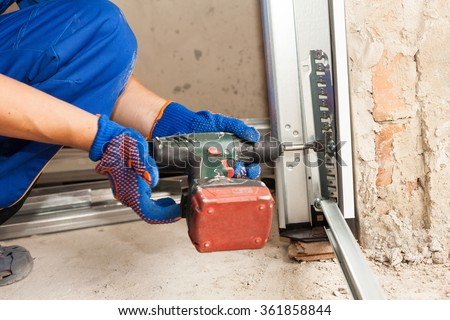 Garage doors installation. Worker use automatic screwdriver  to fix a bolt - stock photo