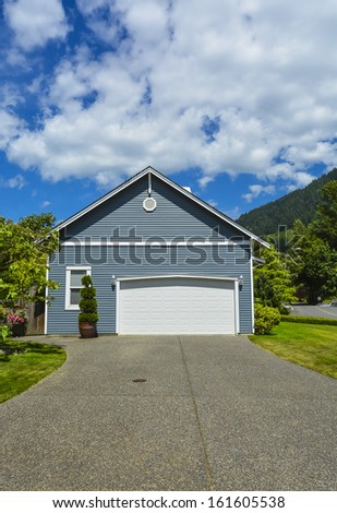 Garage for two cars with concrete driveway and wide gate. North America. - stock photo