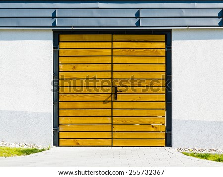 Garage, house or warehouse entry. Yellow wooden door outside.
