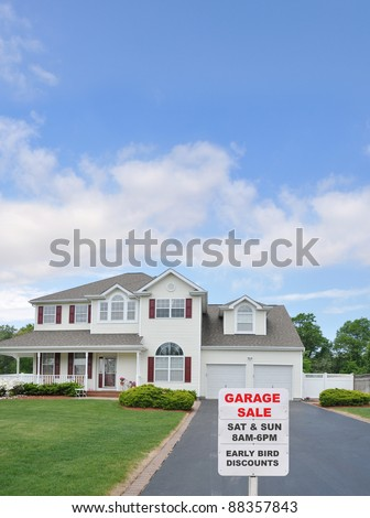 Garage Sale Sign at Driveway edge of large two car garage suburban home on sunny blue cloud sky day in residential neighborhood