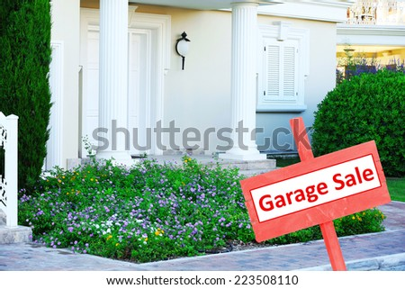 Garage sale sign in front of house - stock photo