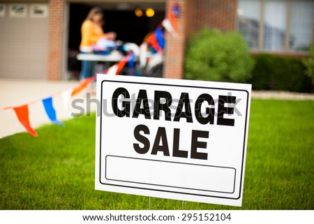 Garage sale sign on the front yard of a suburban house with a woman looking at items on a table. - stock photo