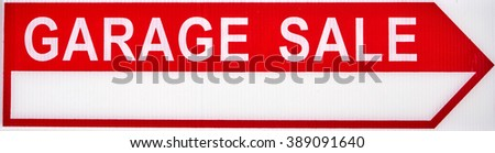 Garage sales red arrow sign on white plastic. - stock photo