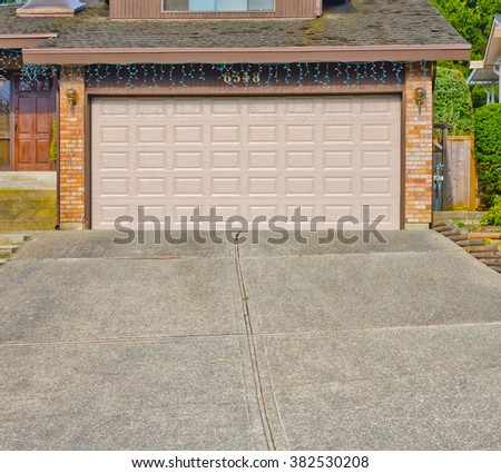 Garage with wide, long driveway. - stock photo