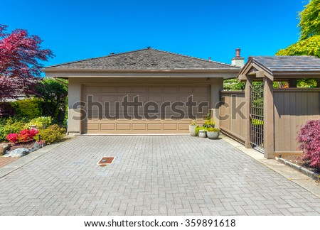 Garage with wide, long nicely paved driveway.