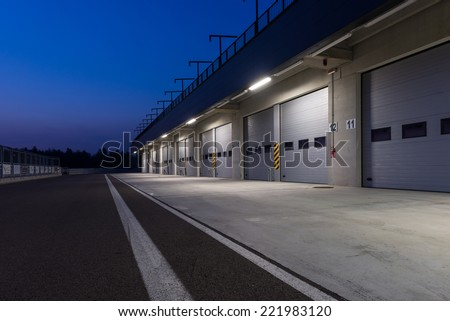 Garages in race circuit. Night time. - stock photo