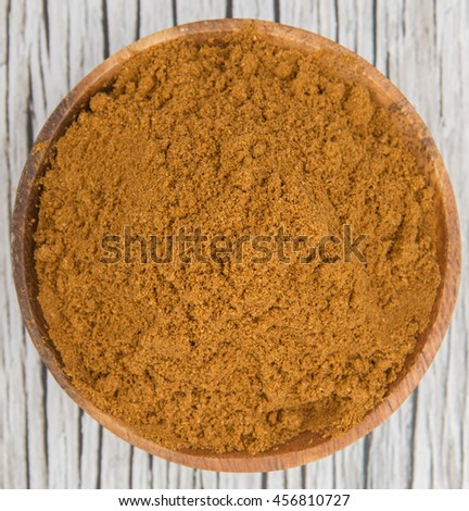 Garam masala or mix spices blend in a wooden bowl over wooden background