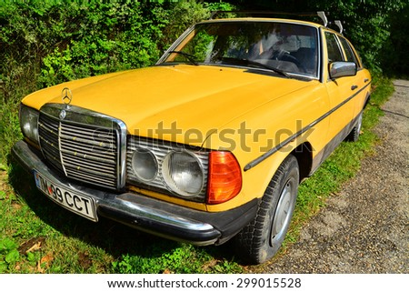 garana, romania - 12 july: an old, retro, yellow mercedes benz parked at the side of the road. shot taken on july 12th, 2014 - stock photo