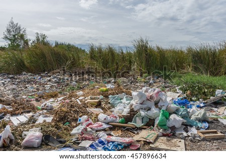 Garbage and junk dump to the landfill in field it illegal, hazardous and dangerous for environment - stock photo