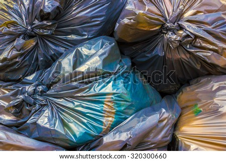 Garbage bags colored stacked and ready to be picked. - stock photo