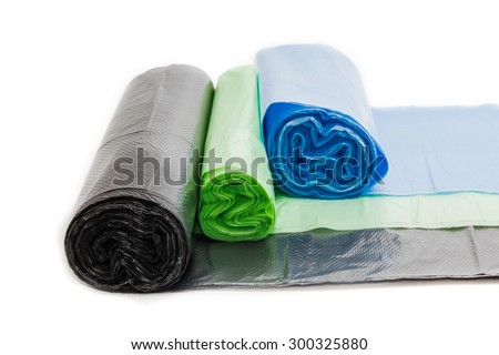 Garbage bags in rolls of different sizes and colors not harmful to the environment on a light background. Isolation. - stock photo