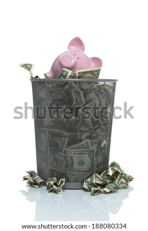 Garbage can full of money spilling over with piggy bank in it - stock photo
