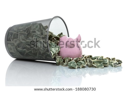 Garbage can full of money tipped on its side with piggy bank in it - stock photo