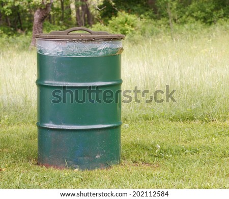 Garbage Can in park setting. - stock photo